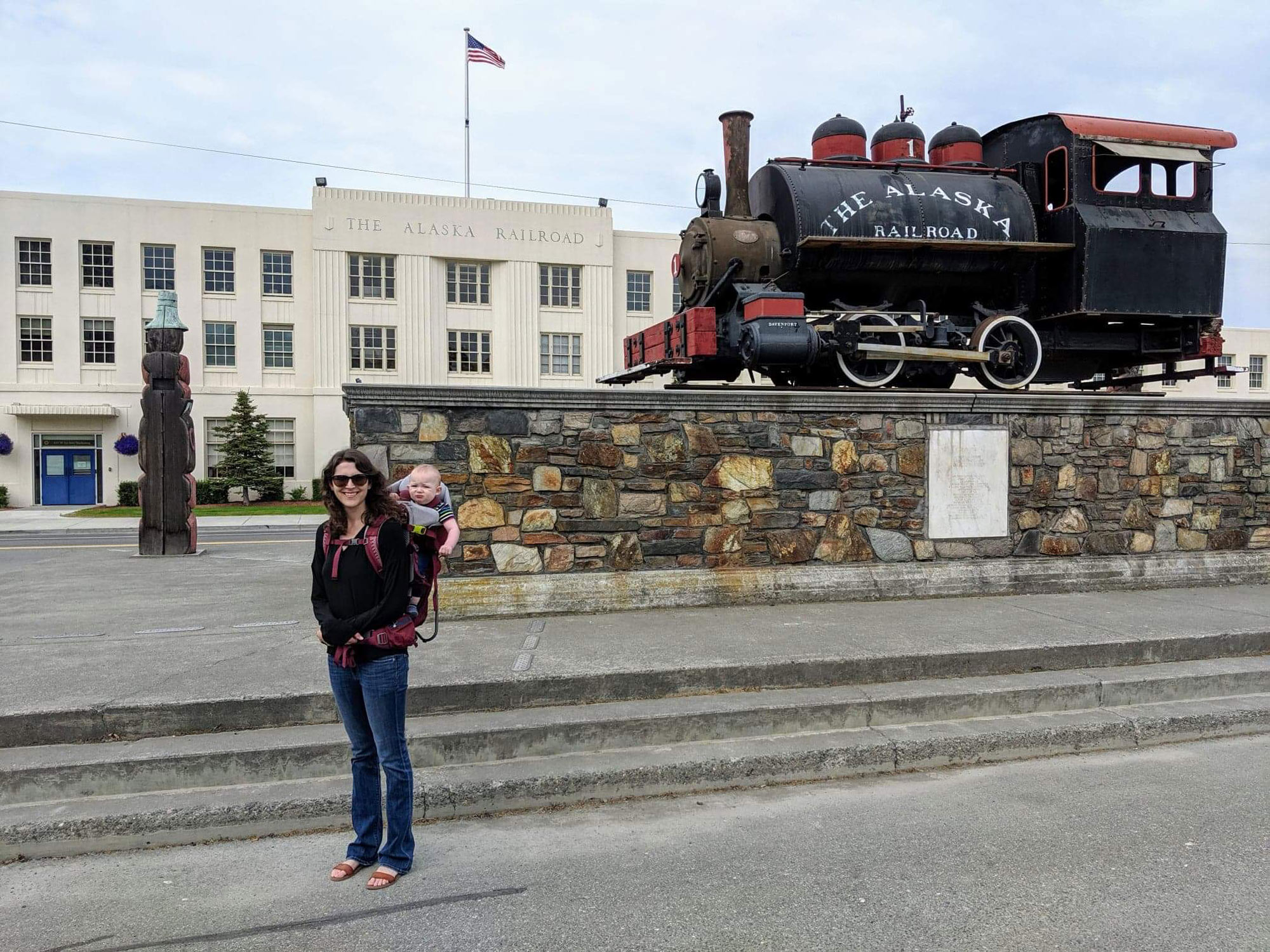 Alexandria Boley with a baby in a backpack in front of The Alaska Railroad building
